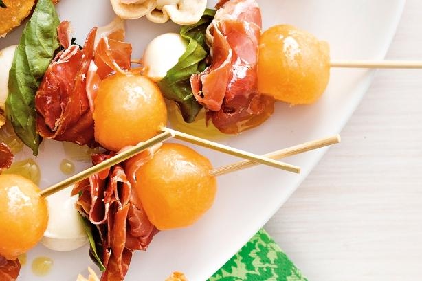 Рецепт канапе фруктовое: Дыня и прошутто на шпажках.